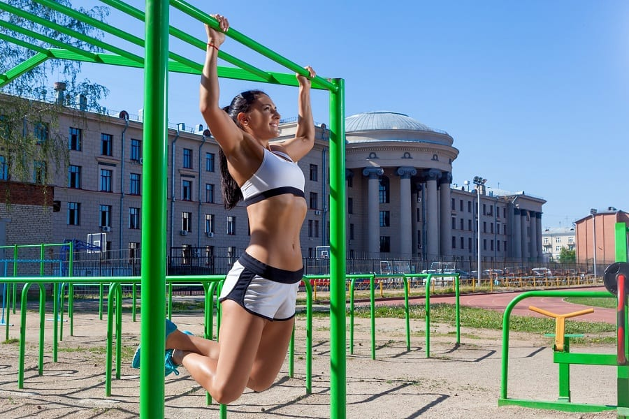 Young athletic brunette woman doing pull-up on a sports horizontal bar in a stadium on a summer day